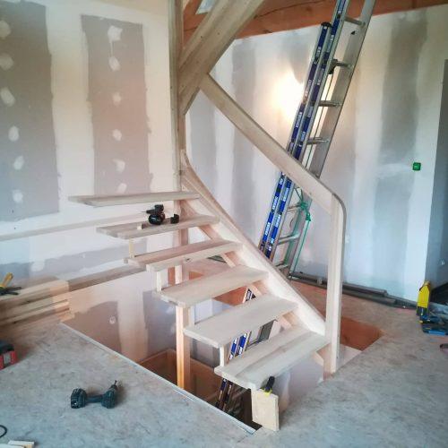 Escalier à double quart tournant sur limons avec rambarde bois main courante intégré au limon claustras garde corps ajouré et balustres barreaux bois